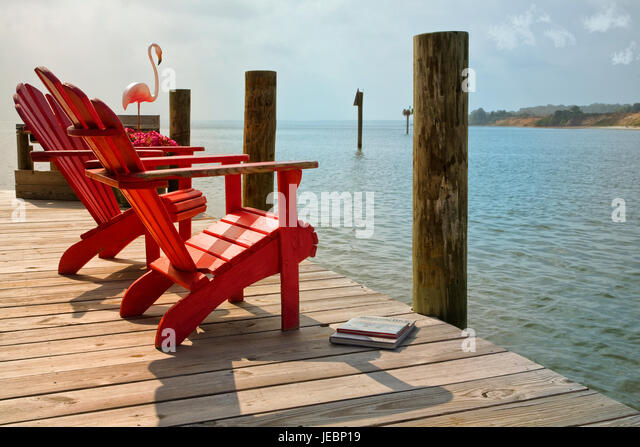 Red Adirondack Chairs Overlooking Bay From Dock   Stock Image