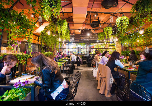 Patrons enjoying a meal inside the Aoyama Flower Market Tea House in Aoyama, Tokyo, Japan - Stock Image