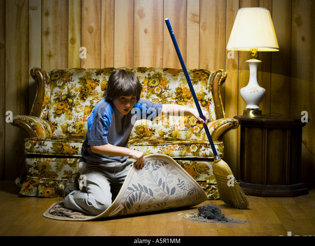 Attractive Boy Sweeping Dirt Under Rug   Stock Image
