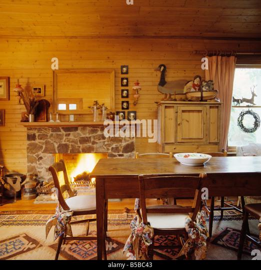 Antiken Holztisch Und Stühle Mit Cremefarbenen Kissen Im Rustikalen  Speisesaal Mit Kamin Und Hölzernen Stockbild