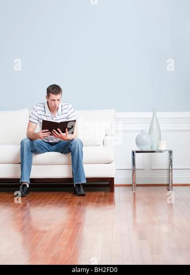 Man Sitzt Und Liest Auf Einer Weissen Couch In Seinem Wohnzimmer Hochformat Stockbild
