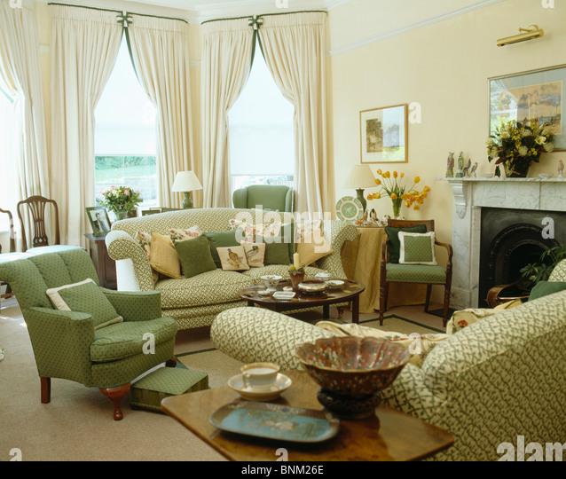 Grüne Sessel Und Sofa Mit Kissen Im Traditionellen Wohnzimmer Mit  Cremefarbenen Vorhängen Auf Erker Aufgetürmt Stockbild