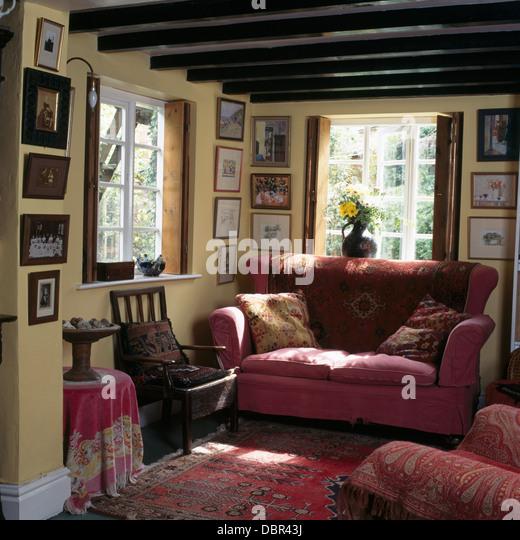 Rosa Sofa Vor Fenster In Holzbalken Ferienhaus Wohnzimmer Mit Sammlung Von Kleinen Bildern An Den Wnden