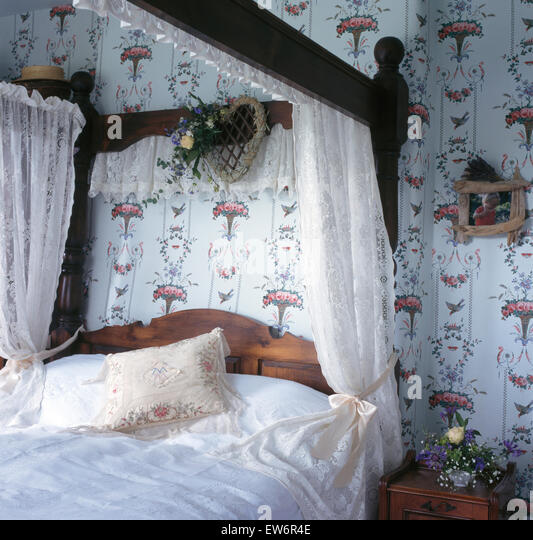 weie spitzen vorhnge am himmelbett in neunziger jahre ferienhaus schlafzimmer mit gemusterten tapeten stockbild - Gotische Himmelbettvorhnge