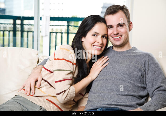 a young couple relaxing on a sofa stockfotos a young couple relaxing on a sofa bilder seite. Black Bedroom Furniture Sets. Home Design Ideas