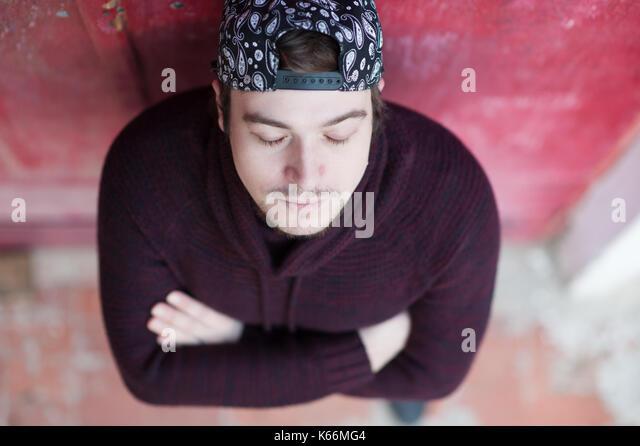 d57418b929a4 Entspannende junger Mann mit geschlossenen Augen das Tragen einer Baseball  Cap und Pullover auf der roten