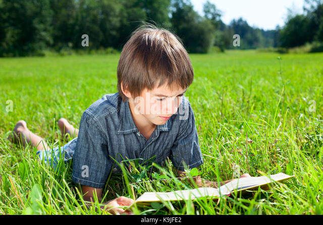 cute kid reading book lying stockfotos cute kid reading book lying bilder alamy. Black Bedroom Furniture Sets. Home Design Ideas