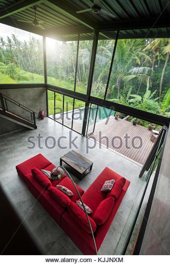 Modernes, Minimalistisches Wohnzimmer Mit Roten Couch In Zeitgenössischem  Design Haus Mit Glasfassade, Umgeben Stockbild